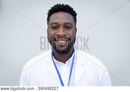 Portrait of confident African American male medical professional wearing lab coat smiling to camera. Social distancing and hygiene in the workplace during Coronavirus Covid 19 pandemic.