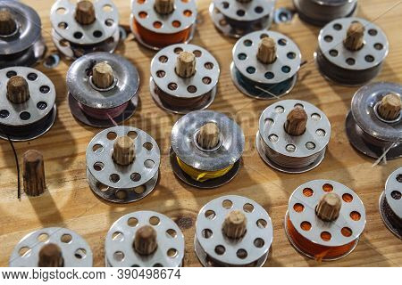 Many Thread-filled Bobbins Resting On A Rack For Clothes Manufacturing.