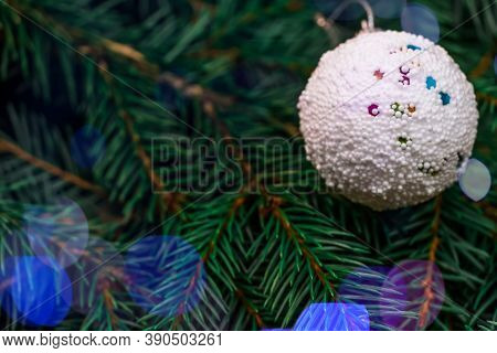 White Christmas Ball On The Branch Of A Christmas Tree Close-up. Beautiful, Bright Christmas, New Ye