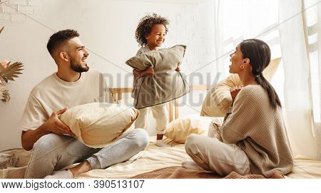 Happy Family Multi Ethnic Mother, Father And Son  Laughing, Playing, Fights Pillows And Jumping In B