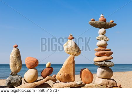 Several Rock Zen Pyramids Of Colorful Pebbles On A Beach On The Background Of The Sea. Concept Of Ba
