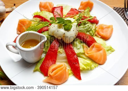 Salad With Baked Pepper, Salmon And Poached Egg. Served On A White Plate, Top View