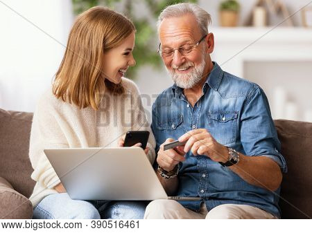 Positive Young Female With Gray Haired Father Sitting On Sofa With Laptop And Using Smartphone While