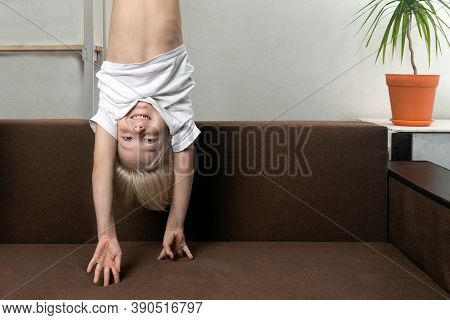 Boy Is Upside Down Over Sofa. Funny Child Hangs Upside Down