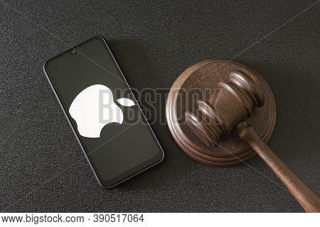 Kharkov, Ukraine - June 25, 2020: Apple Logo On Phone Display Next To Judges Gavel. Top View. Apple