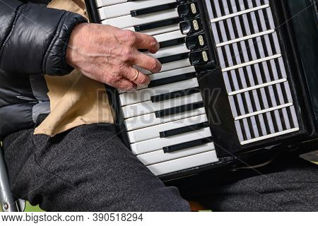 An Elderly Man Plays The Accordion. Close-up Musician Playing The Accordion On The Street.