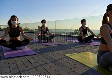 Multiethnic Young Women Group Wear Face Masks Meditate In Lotus Pose Keep Social Distance At Retreat