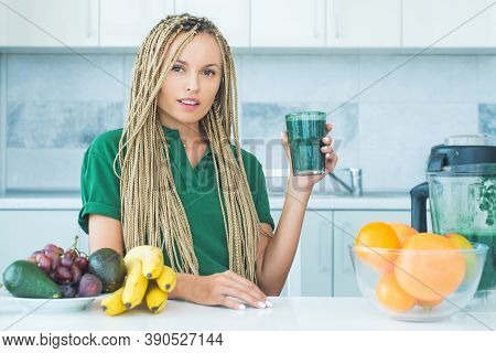 Positive Woman Hold Cup Of Fresh Green Smoothie. Eco Lifestyle. Young Woman Drinking Green Smoothie