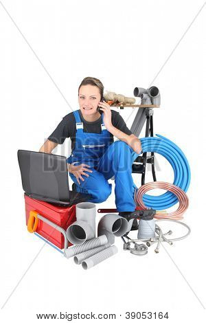 Tradeswoman surrounded by building materials and technology