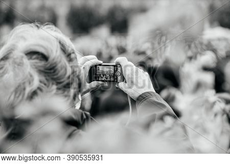 Strasbourg, France - Oct19, 2020: Black And White Image Of Senior Woman Taking Photos Of Protestors