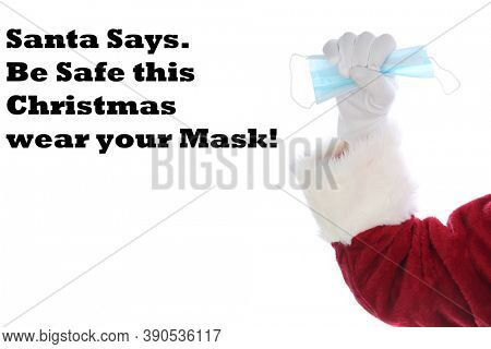 Covid-19 Santa Claus. Santa Claus Arm holds a paper face mask as a Christmas Gift. Isolated on white. Room for text. Covid-19 is Dangerous, Wear your mask.