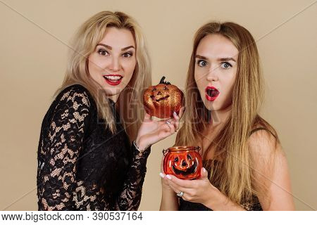 Girlfriends Are Celebrating Halloween In The Studio. Two Young Women Are Holding Pumpkin-shaped Cand