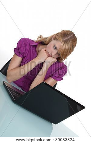 Office worker looking sadly at her laptop