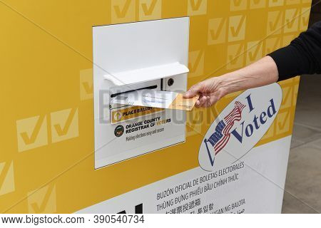 IRVINE, CALIFORNIA - 18 OCT 2020: Woman placing mail in ballot in an Official Ballot Drop Box at a public park, Irvine, Orange County, California.