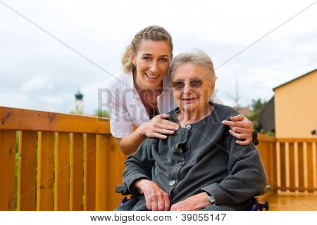 Young nurse and female senior in a wheel chair going for a walk