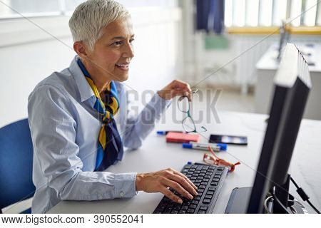 A female professor typing on a computer at a lecture in the university classroom. Professor working at the college. Education, college, university, learning and people concept