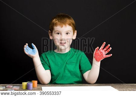 Portrait Of A Small Red-haired Boy Draws On Paper Using Paints Of Different Colors, The Boy Draws Wi