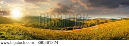 Mountainous Countryside Landscape At Sunset. Panorama Of A Grassy Rural Field On The Hill In Evening