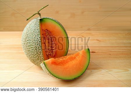 Orange Color Fresh Ripe Juicy Muskmelon With A Slice From Whole Fruit Isolated On A Wooden Table