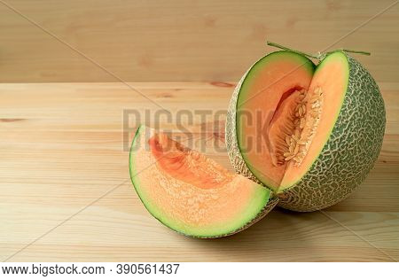Slice Of Fresh Ripe Muskmelon Sliced From The Whole Fruit Isolated On A Wooden Table