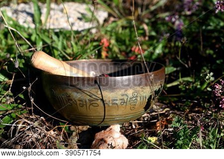 Tibetan Singing Bowl In The Grass. Translation Of Mantras. Transform Your Impure Body, Speech And Mi