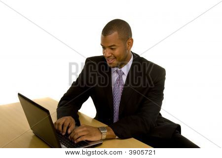 A black man in a business suit working at a desk on a laptop poster