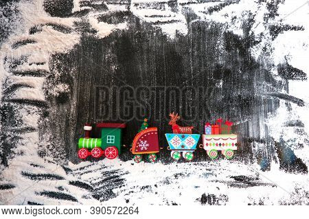 A Toy Wooden Train Carries Gifts And Christmas Paraphernalia On A Dark, Snow-covered Background. Ima