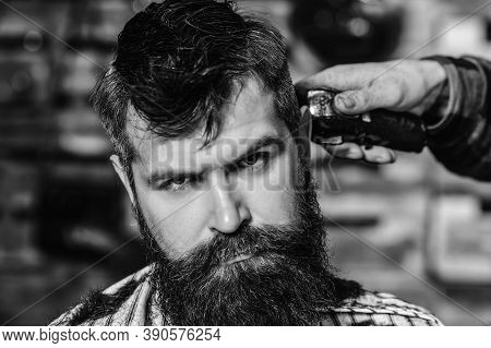 Hairstylist Serving Client. Barber Making Haircut Using Machine. Stylish Bearded Man In Barber Shop.