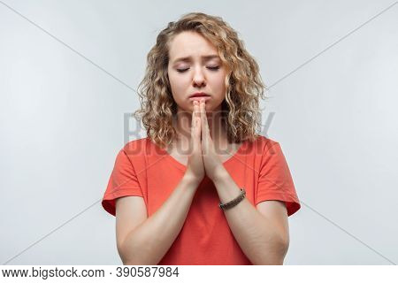 Portrait Of Joyous Blonde Girl With Curly Hair In Casual T Shirt Keeping Palms Together And Praying.