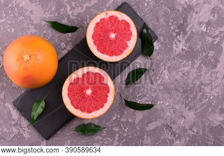 Grapefruit And Grapefruit Wedges On A Gray Background. Flat Lay. Copy Space.