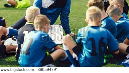 Coaching Kids In Team Sports. Coach Explaining Tactics Details Using White Soccer Tactics Board. Chi