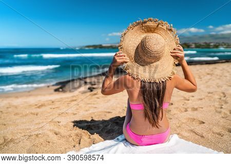 Beach girl in pink bikini wearing floppy hat sun tanning on Beach holiday in Caribbean destination sunbathing relaxing with view on ocean.