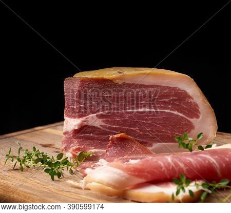 Large Piece Of Jerky Prosciutto On Brown Wooden Board, Black Background