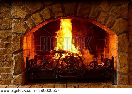 Warm Cozy Fireplace With Real Wood Burning In It. Cozy Winter Concept. Christmas And Travel Backgrou