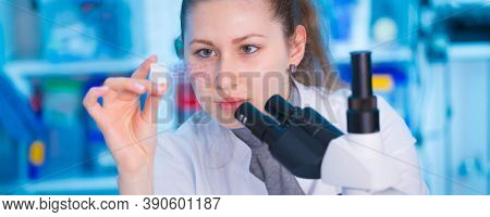 Young woman scientist looking a microscope in a laboratory. Girl scientist doing microbiological research