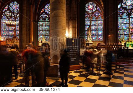 Paris, France - November 20, 2018: Interior of Notre Dame de Paris cathedral with stained glass windows and many tourists. Long exposure photo with blurry people