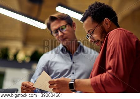 Two Focused Diverse Business Colleagues Analyzing Document And Discussing Something While Standing I