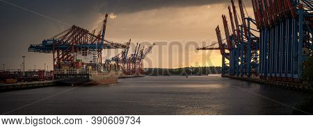 Sunset In The Harbor Of Hamburg At Container Terminal
