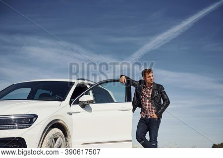 Man In Black Leather Jacket Stands Near His Parked White Car Outdoors Against Blue Sky.
