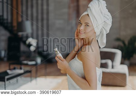 Indoor Shot Of Pretty European Woman With Healthy Glowing Skin, Minimal Makeup, Holds Bottle Of Body