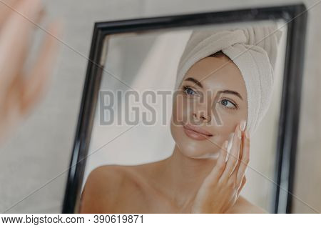 Young Naked European Woman Touches Soft Skin On Face, Looks At Herself In Bathroom Mirror, Wears Wra