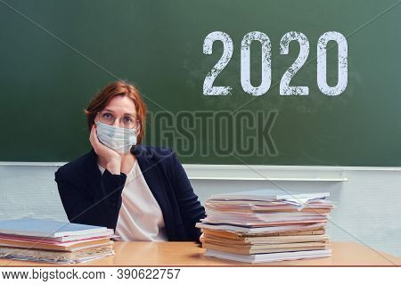 Woman Teacher In Medical Mask Near The School Blackboard With Chalk Text 2020. Concept Of Problems D