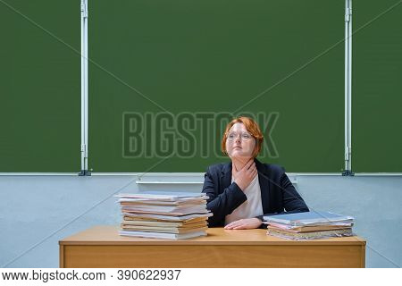 A Teacher Holds A Sore Throat In A School Classroom. Voice Problems, Coughing And Throat Diseases, C