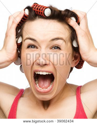 Young woman is screaming in terror holding her head with hands while wearing hair-rollers, isolated over white