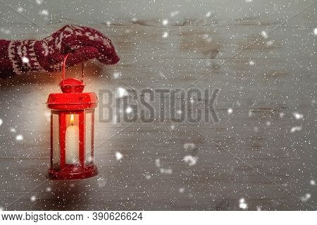 Hand In Glove Holding Christmas Lantern And Falling Snow On Wooden Wall With Copy Space. Hand In Kni