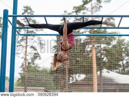 Fit Blond Attractive Woman Doing Split Hanging Upside Down In The Sports Area Outdoor In Summer, Sel