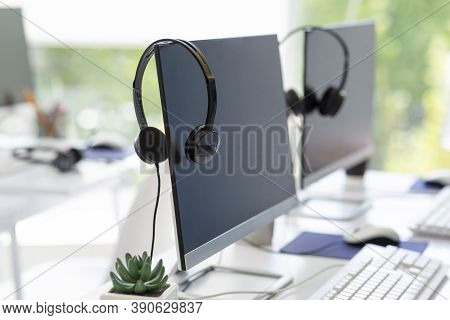 Computer Monitor With Empty Space For Your Design And Voip Headset On Desk At Modern Office. Contemp