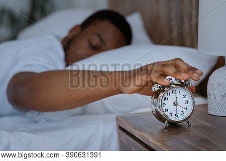 Sleepy African Man Awakening Early In The Morning Turning Off Alarm Clock Lying In Bed At Home, Focu