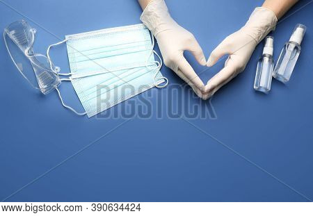 Person In Gloves Showing Heart Gesture Surrounded By Medical Items On Blue Background, Top View. Spa