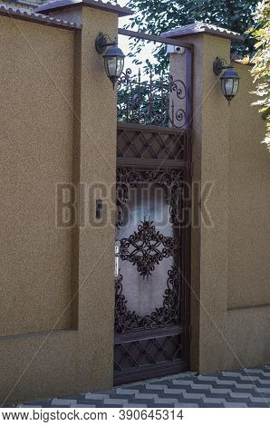 Metal Entrance Door And A High Fence With Video Surveillance Camera. Entrance To The Territory Of  P
